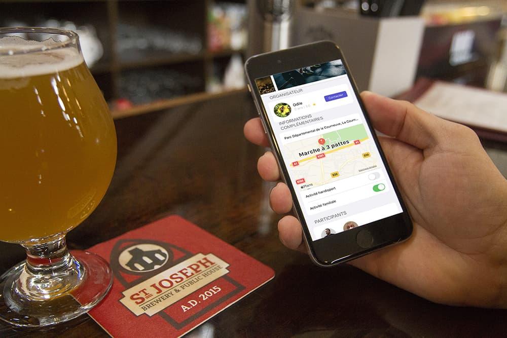 Une main qui tient un smartphone à la terrasse d'un café